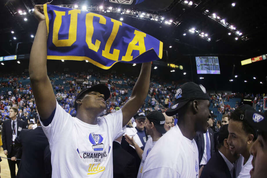 UCLA's Tony Parker holds up a UCLA banner after UCLA defeated Arizona 75-71 in the championship game of the NCAA Pac-12 conference college basketball tournament, Saturday, March 15, 2014, in Las Vegas. (AP Photo/Julie Jacobson)