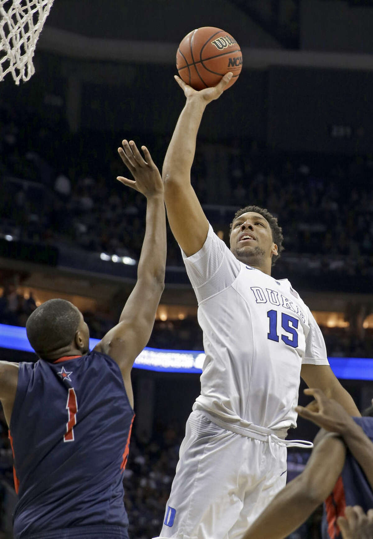 Duke's Jahlil Okafor (15) shoots over Robert Morris's Lionel Gomis (1) during the first half of an NCAA tournament college basketball game in the Round of 64 in Charlotte, N.C., Friday, March 20, 2015. (AP Photo/Gerald Herbert)