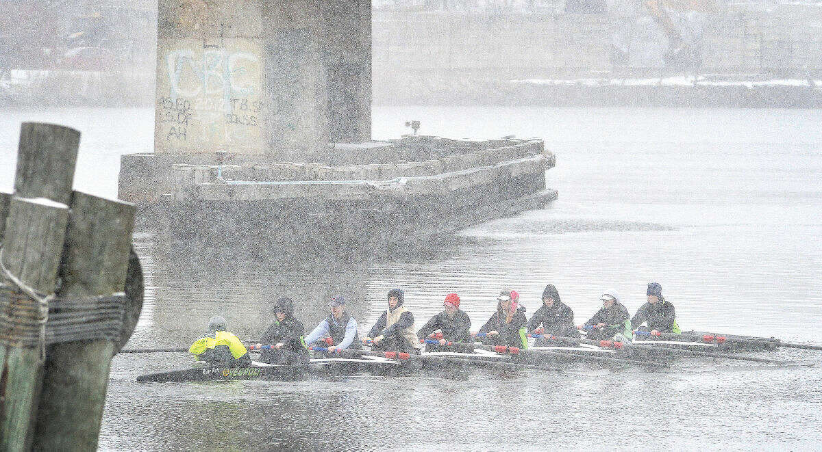 Hour Photo/Alex von Kleydorff Rowers with The Connecticut Boat Club make their way up the Norwalk River on Friday, with water temperatures in the 30's and snow falling steadily on the first day of spring.