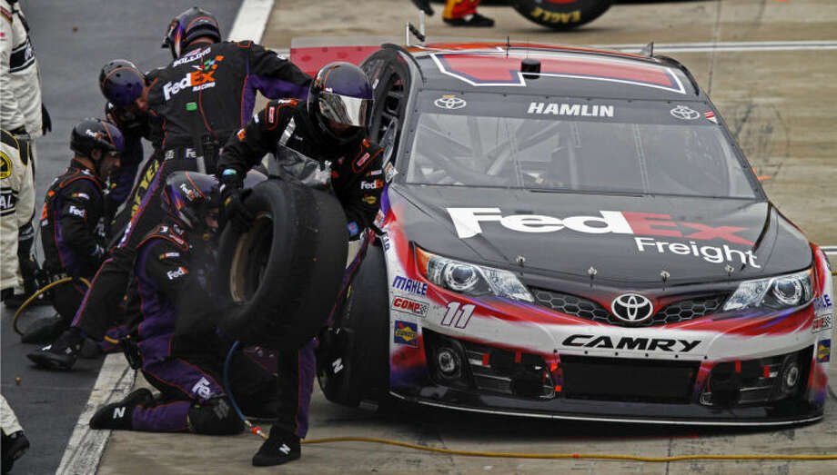 The team of driver Denny Hamlin (11) works on his car during the NASCAR Sprint Cup series auto race at Bristol Motor Speedway, Sunday, March 16, 2014, in Bristol, Tenn. (AP Photo/Wade Payne)