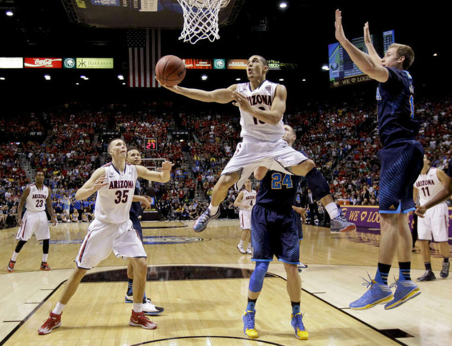 Arizona's Nick Johnson, center, puts up a reverse layup against UCLA in the second half during the championship game of the NCAA Pac-12 conference college basketball tournament, Saturday, March 15, 2014, in Las Vegas. UCLA won 75-71. (AP Photo/Julie Jacobson)