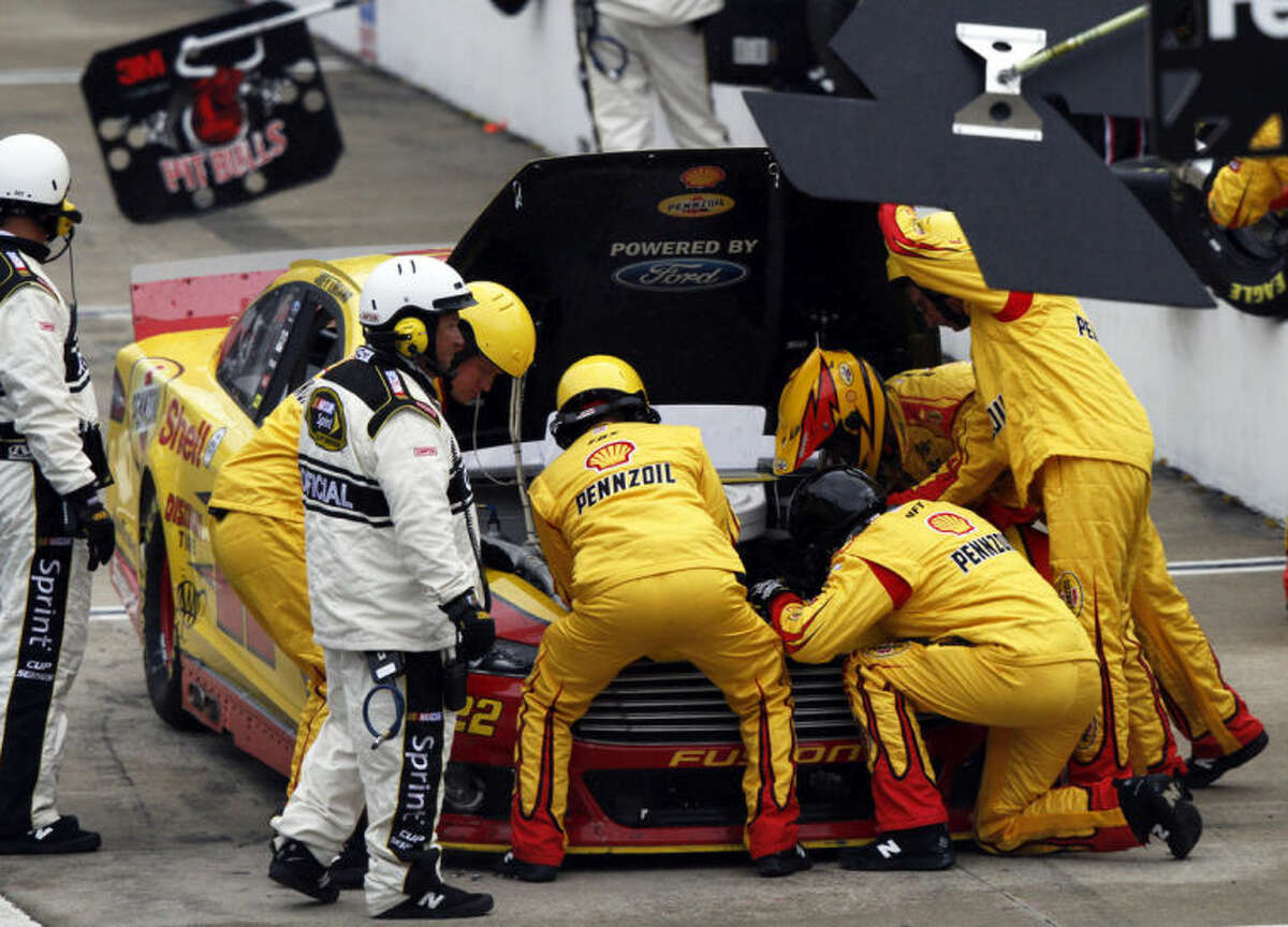 The team of Joey Logano (22) works on his car after the power steering went out during the NASCAR Sprint Cup Series auto race at Bristol Motor Speedway, Sunday, March 16, 2014, in Bristol, Tenn. (AP Photo/Wade Payne)