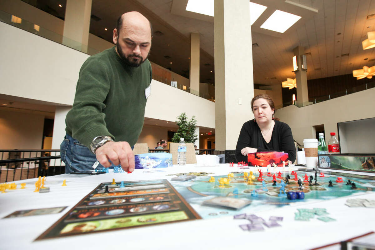 """Hour photo/Chris Palermo. Cassini and Mindy Kyrkos play the board game """"Cyclades"""" during ConnCon at the Stamford Sheraton Hotel Sunday."""