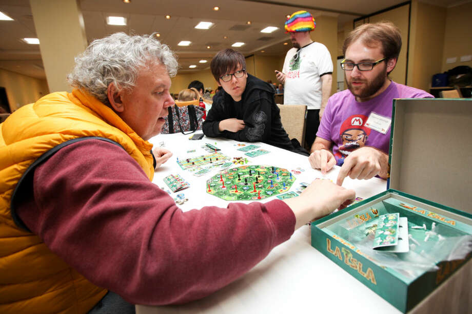 "Hour photo/Chris Palermo. Todd Redden, Nick Hong, and Connor Jennings play the board game ""La Isla"" during ConnCon at the Stamford Sheraton Hotel Sunday."
