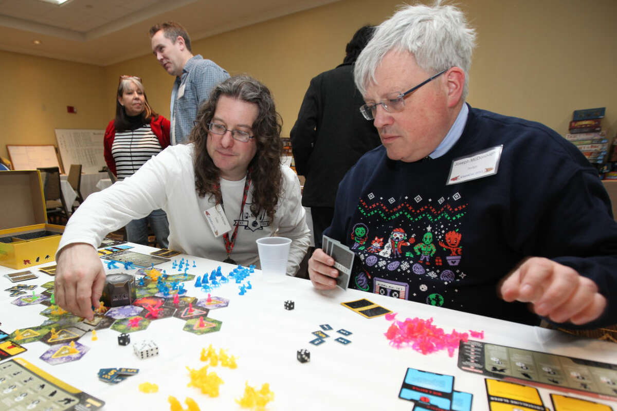 """Hour photo/Chris Palermo. Avri Klemer and Joseph McDonough play the board game """"Nexus Ops"""" during ConnCon at the Stamford Sheraton Hotel Sunday."""