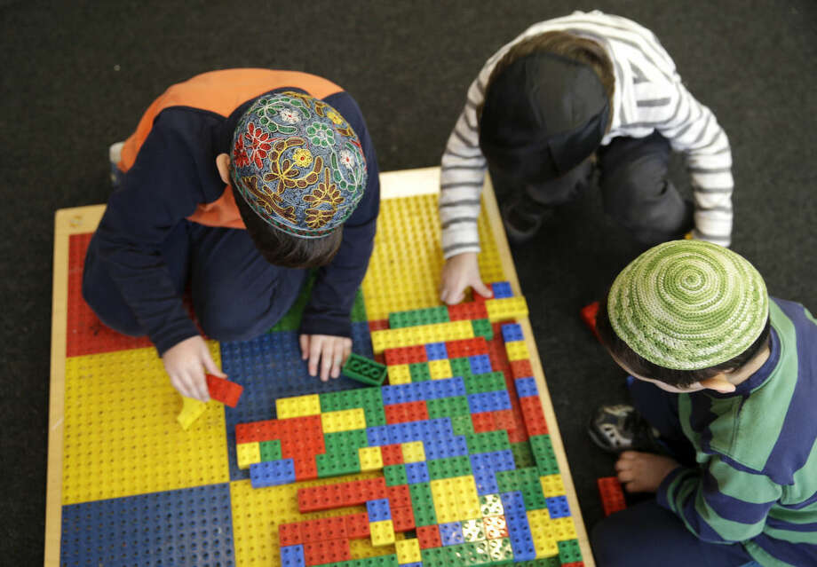 "Jewish children wear skull caps, or kippah, in their pre-kindergarten class at the Al & Sonny Gindi Barkai Yeshivah in Brooklyn, New York, Wednesday, March 11, 2015. Starting next September, New York City pre-K classes will be permitted to break in the middle of the day for ""non-program"" activities such as prayer. Civil liberties groups say the prayer break in a publicly funded classroom may violate the constitutional separation of church and state. (AP Photo/Seth Wenig)"