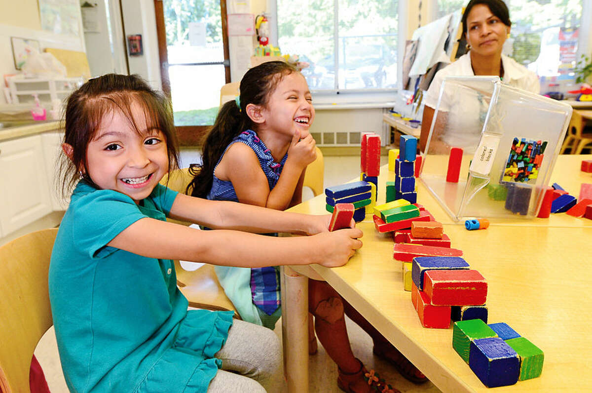 Four-year-old students at Palmer's Hill Child Development Center in Stamford, Alison Sandoval and Cheryl Teo, play with blocks in class Friday. The Child Care Learning Centers recently honored two of their most successful