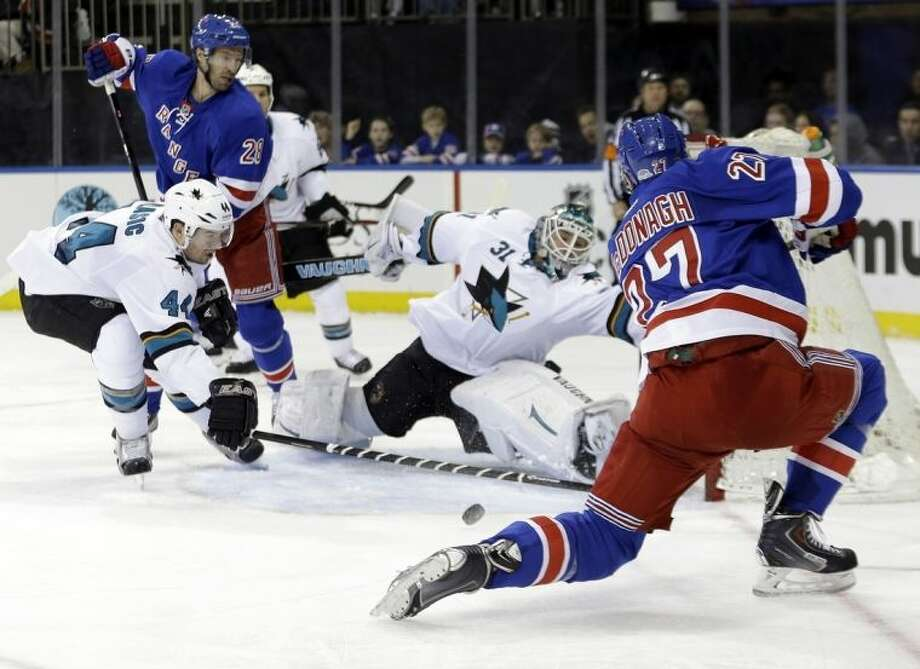 San Jose Sharks goalie Antti Niemi (31), of Finland, and Marc-Edouard Vlasic (44) stop a shot on goal by New York Rangers' Ryan McDonagh (27) during the second period of an NHL hockey game on Sunday, March 16, 2014, in New York. (AP Photo/Frank Franklin II)