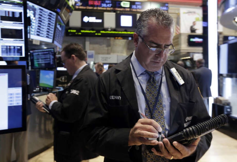 Trader Kenneth Polcari, right, works on the floor of the New York Stock Exchange Monday, March 17, 2014. Stocks are sharply higher in early trading following news that output at U.S. factories surged last month. (AP Photo/Richard Drew)