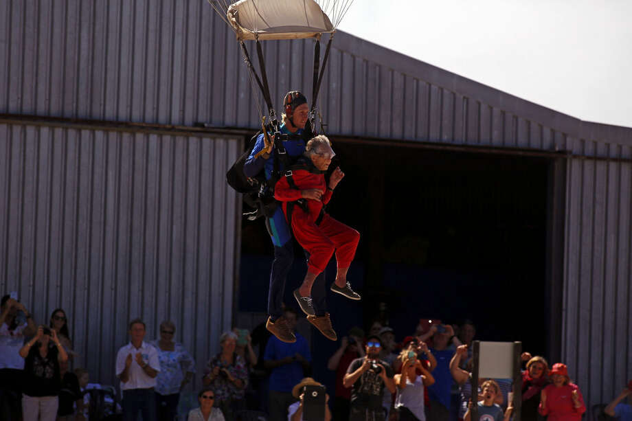 Centenarian Georgina Harwood, center right, gestures as she lands with Jason Baker, centre left, after her tandem parachute jump forming part of her birthday celebrations, in Cape Town, South Africa, Saturday, March 14, 2015. Harwood, who celebrated her 100th birthday on Tuesday, completed her third tandem parachute jump in front of family and friends. (AP Photo/Schalk van Zuydam)