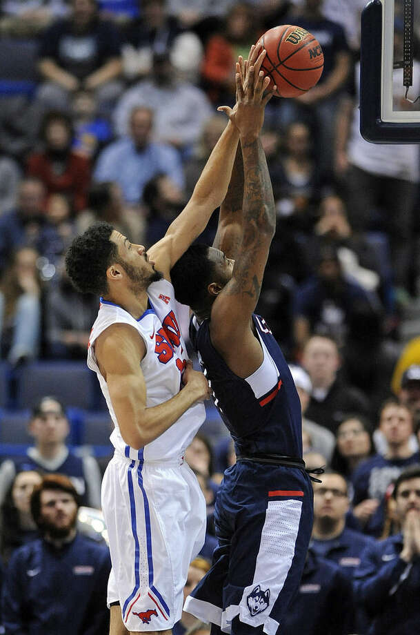 SMU's Cannen Cunningham, left, shoots over Connecticut's Phillip Nolan during the first half of an NCAA college basketball game in the finals of the American Athletic Conference tournament in Hartford, Conn., on Sunday, March 15, 2015. (AP Photo/Fred Beckham)