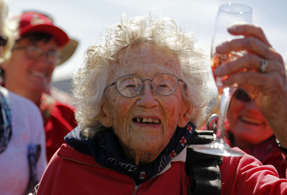 Centenarian Georgina Harwood, celebrates after her tandem parachute jump forming part of her birthday celebrations, in Cape Town, South Africa, Saturday, March 14, 2015. Harwood, who celebrated her 100th birthday on Tuesday, completed her third tandem parachute jump in front of family and friends. (AP Photo/Schalk van Zuydam)