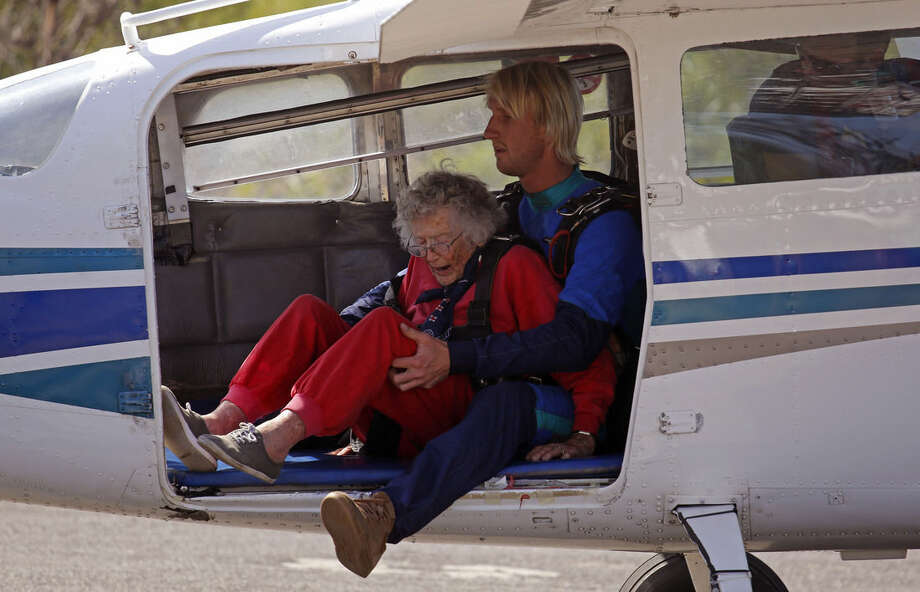 Centenarian Georgina Harwood, sits inside an airplane with Jason Baker, right, before her tandem parachute jump forming part of her birthday celebrations, in Cape Town, South Africa, Saturday, March 14, 2015. Harwood, who celebrated her 100th birthday on Tuesday, completed her third tandem parachute jump in front of family and friends. (AP Photo/Schalk van Zuydam)