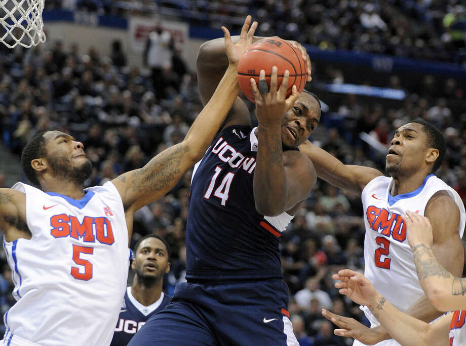 Connecticut's Rakim Lubin (14) fights for a rebound with SMU's Markus Kennedy, left, and Yanick Moreira during the first half of an NCAA college basketball game in the finals of the American Athletic Conference tournament in Hartford, Conn., on Sunday, March 15, 2015. (AP Photo/Fred Beckham)