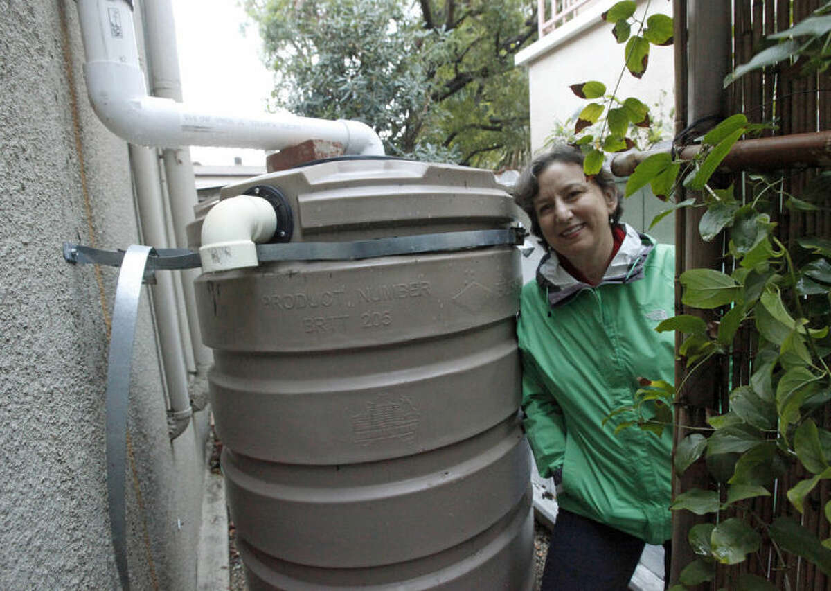 In this Feb. 28, 2014 photo, Santa Monica, Calif., resident Josephine Miller stands next to her 200-gallon water storage tank that collects rain from her home's roof to water her garden. With California in a drought, some communities in recent years have turned to water conservation measures in an effort to cut down on imported water. (AP Photo/Reed Saxon)