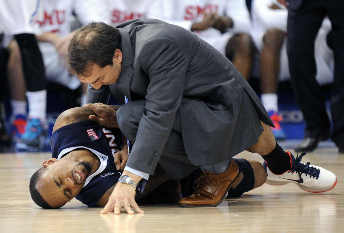 Connecticut athletic trainer James Doran evaluates Ryan Boatright during the second half of an NCAA college basketball game against SMU in the finals of the American Athletic Conference tournament in Hartford, Conn., Sunday, March 15, 2015. SMU won the game 62-54. (AP Photo/Fred Beckham)