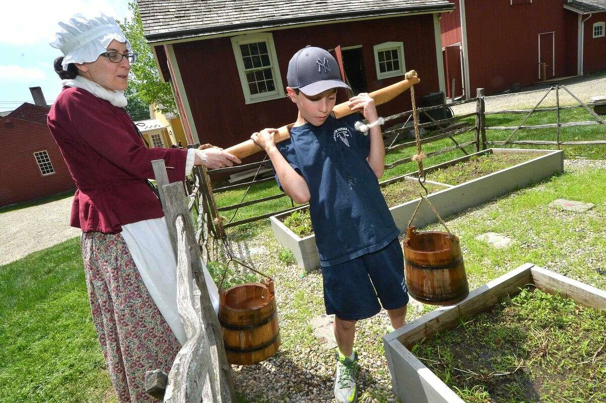 Educatur Allison Reznik helps Our Lady of Fatima School fifth-grader Anthony Bonaddio get the yoke of water into the garden during a program at the Wilton Historical Society.
