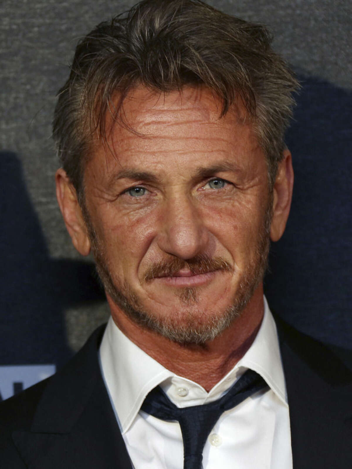 """FILE - In this Feb. 16, 2015 file photo, actor Sean Penn arrives for the World Premiere of """"The Gunman"""" at the BFI south bank cinema, in London. Penn surfs, shoots, sprints, punches and fights for his life in the geopolitical thriller in theaters on Friday, March 20, 2015. (Photo by Joel Ryan/Invision/AP, File)"""