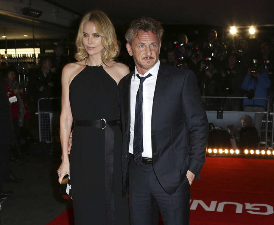 "FILE - In this Feb. 16, 2015 file photo, actors Sean Penn, right, and Charlize Theron arrive for the World Premiere of ""The Gunman"" at the BFI south bank cinema, in London. Penn surfs, shoots, sprints, punches and fights for his life in the geopolitical thriller in theaters on Friday, March 20, 2015. (Photo by Joel Ryan/Invision/AP, File)"