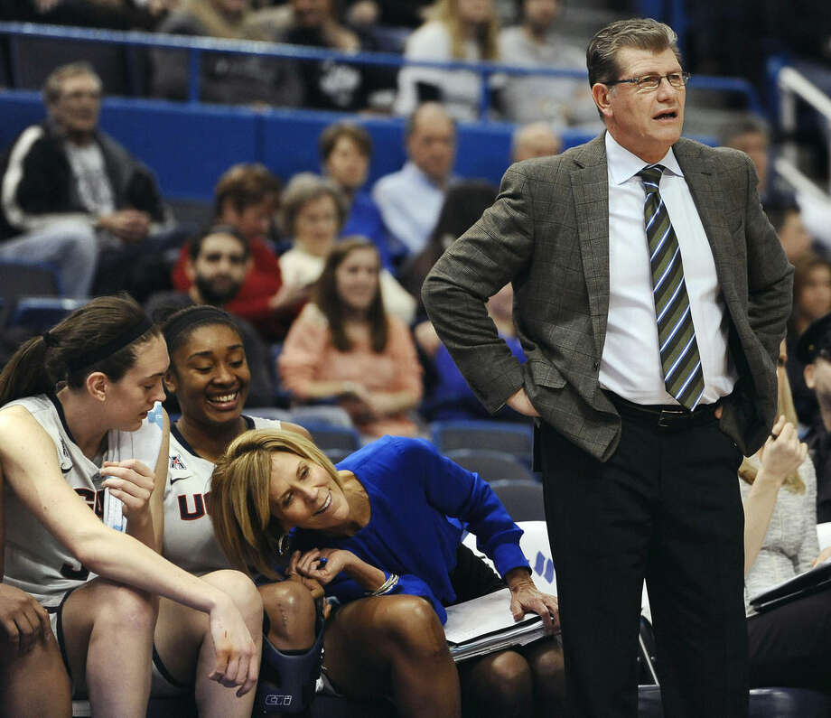 FILE - In this Jan. 28, 2015, file photo, Connecticut associate head coach Chris Dailey, center, leans over to see the play around head coach Geno Auriemma, right, as players Breanna Stewart, left, and Morgan Tuck look on during the second half of an NCAA college basketball game in Hartford, Conn. Dailey has turned down numerous head coaching opportunities to remain Auriemma's assistant at UConn for 30 years. (AP Photo/Jessica Hill, File)
