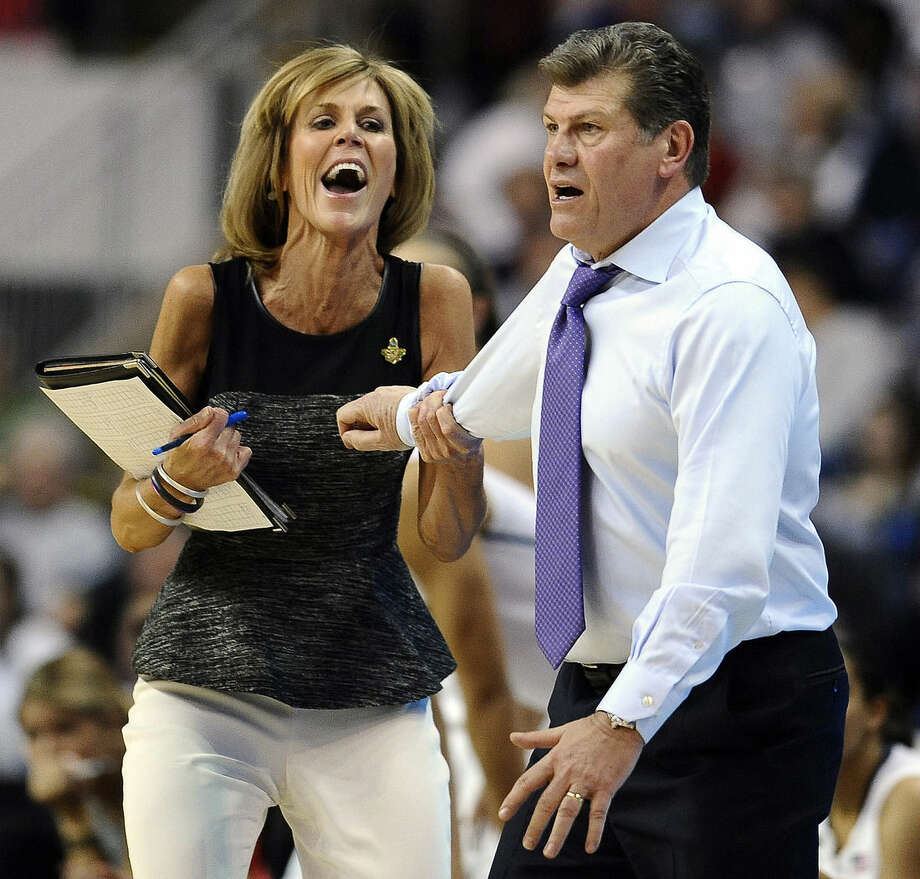 FILE - In this March 30, 2013, file photo, Connecticut associate head coach Chris Dailey, left, pulls back head coach Geno Auriemma, right, during the first half of a regional semifinal against Maryland in the NCAA college basketball tournament in Bridgeport, Conn. Dailey has turned down numerous head coaching opportunities to remain Auriemma's assistant at UConn for 30 years. (AP Photo/Jessica Hill, File)