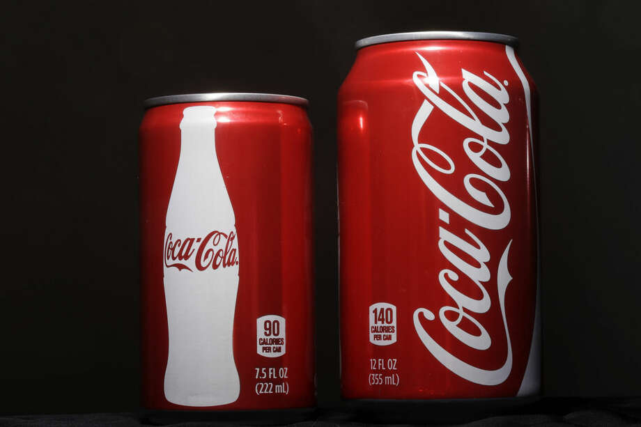 FILE - In this Jan. 12, 2015 file photo, a 7.5-ounce can of Coca-cola, left, is posed next to a 12-ounce can for comparison, in Philadelphia. Coca-cola, which struggles with declining soda consumption in the U.S., is working with fitness and nutrition experts who suggest its cola as a healthy treat. (AP Photo/Matt Rourke, File)