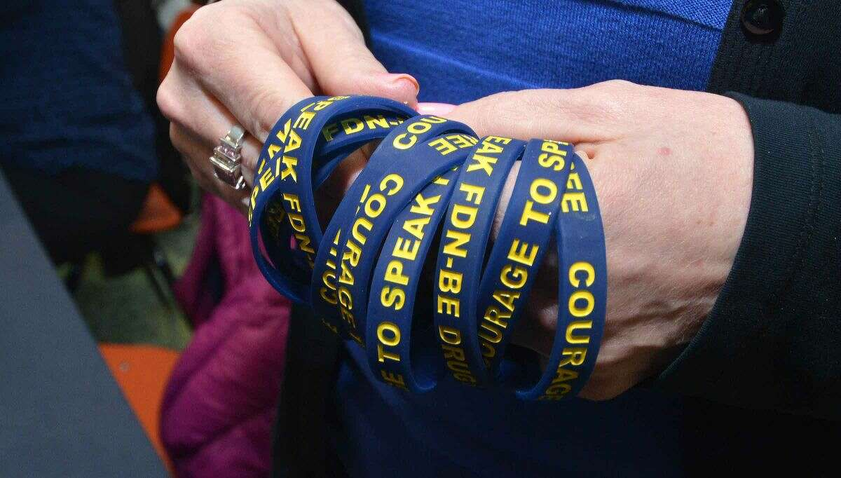 Hour Photo/Alex von Kleydorff Support bracelets are passed out during the Courage to Speak Family Night Program at West Rocks School