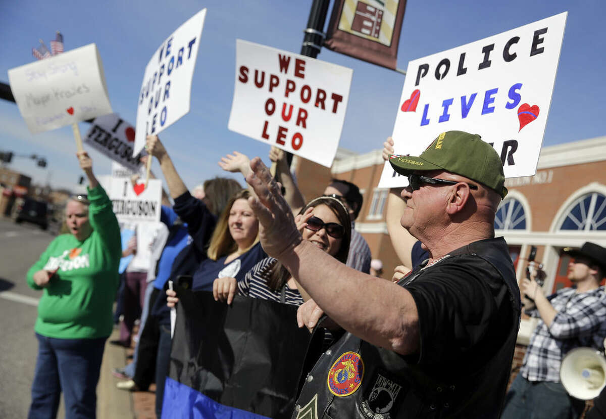 Pro-police demonstrators wave to passing cars as they stand outside the Ferguson Police Department Sunday, March 15, 2015, in Ferguson, Mo. (AP Photo/Jeff Roberson)