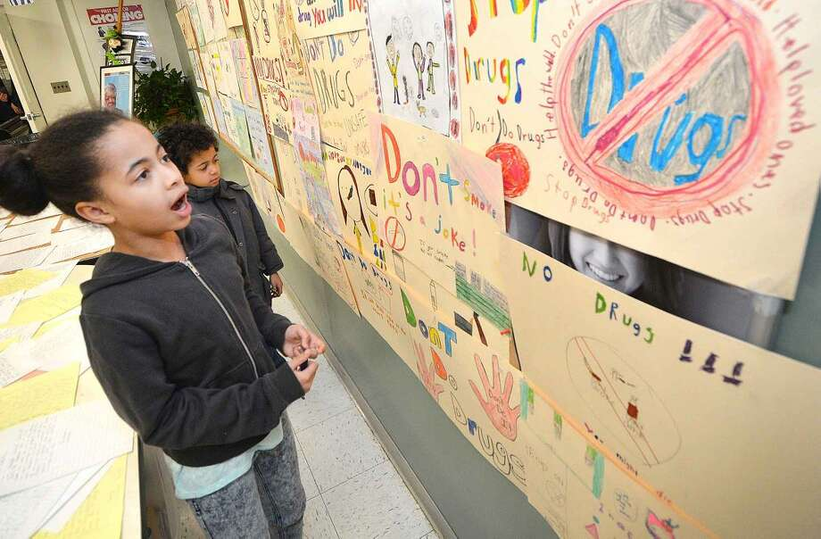 Hour Photo/Alex von Kleydorff Madisyn Davis Ortiz and brother Elijah look for her poster on the wall of Side by Side school artwork during the Courage to Speak Family Night Program at West Rocks School