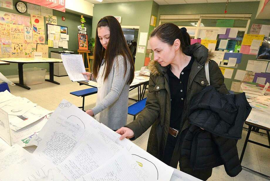 Hour Photo/Alex von Kleydorff Roton School student Victoria Popielarz and her mother Justyna Rydza look over some of the letters from students during the Courage to Speak Family Night Program at West Rocks School