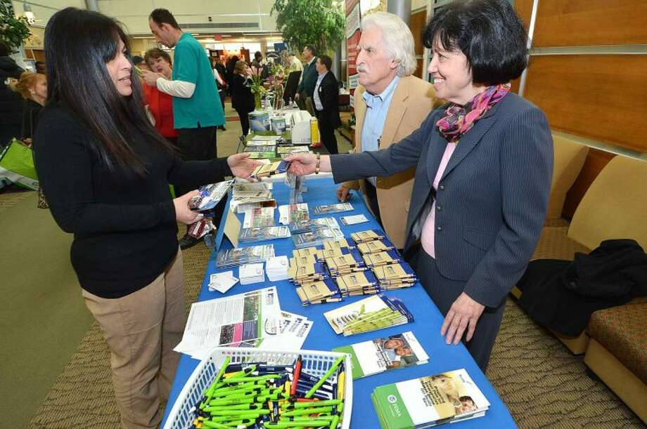 Hour Photo/Alex von Kleydorff Moira Romaine and Walter McLaughlin pass out literature to Jaqueline Santiago about Norwalk Hospitals upcoming event, the 11th annual Whittingham Cancer Center Walk and Sallys Run at Calf pasture, during The Greater Norwalk Chamber of Commerce Multi-Chamber Expo and Networking Event at NCC