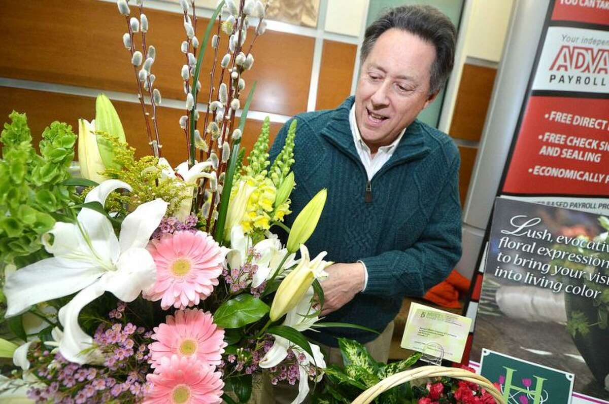 Hour Photo/Alex von Kleydorff Bruce Minoff, owner of Bruce's Flowers straightens a spring arraignment of colorful Gerber Daisy's White Lilly's and Bells of Ireland during The Greater Norwalk Chamber of Commerce Multi-Chamber Expo and Networking Event at NCC