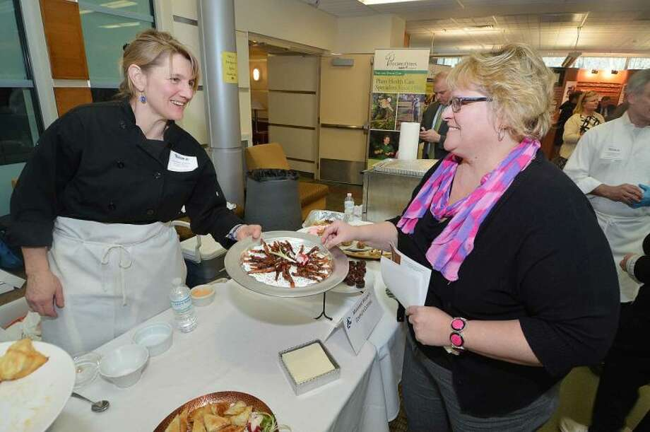 Hour Photo/Alex von Kleydorff Heather Wilson with Marianne Wilson's Complete Catering helps to put some smiles on faces with baked goods spring rolls and their famous Bacon Sticks during The Greater Norwalk Chamber of Commerce Multi-Chamber Expo and Networking Event at NCC