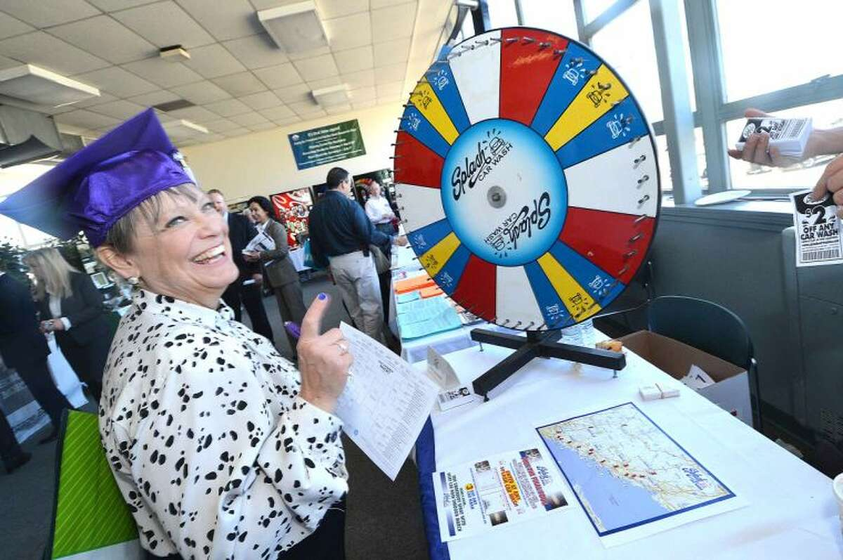 Hour Photo/Alex von Kleydorff Mary Jane Dubner tries her luck with a spin of the wheel at the Splash Car Wash booth during The Greater Norwalk Chamber of Commerce Multi-Chamber Expo and Networking Event at NCC