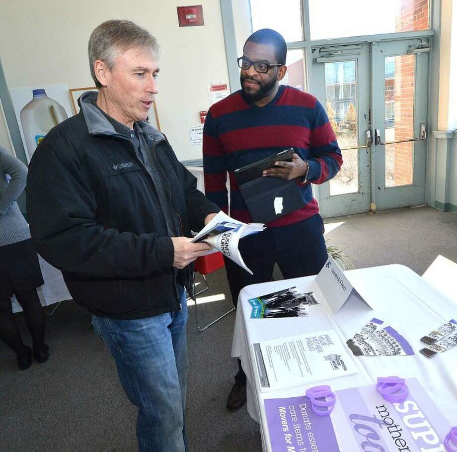 Hour Photo/Alex von Kleydorff Certified Moving Consultant Fredrick Shaw with Two Men and a Truck talks with a potential client about his moving needs during The Greater Norwalk Chamber of Commerce Multi-Chamber Expo and Networking Event at NCC