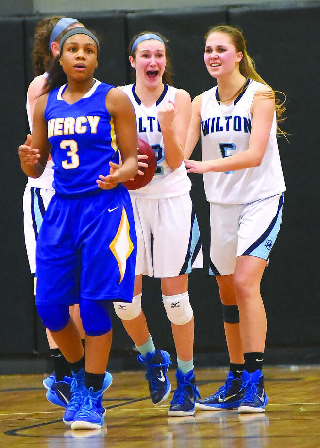 Wilton's Haley English, center, reacts after making a steal with 1.5 seconds left in the game, clinching her team's 55-54 Class LL semifinal win over Mercy on Monday. Wilton's Karen Brosko, right, moves in to celebrate with English while Mercy's Destine Perry reacts with shock. (Hour photo/John Nash)