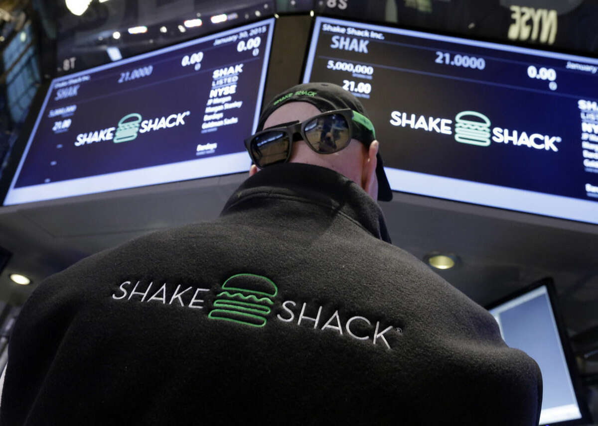 FILE - In this Jan. 30, 2015 file photo, specialist John O'Hara wears Shake Shack promotional hat, sunglasses and vest as he works at his post on the floor of the New York Stock Exchange. Stores, restaurants and media companies should be among the better performers in 2015 as the U.S. economy continues to strengthen and hiring picks up. Low gas prices will put more money in people's pockets, also helping consumer-focused stocks. (AP Photo/Richard Drew, File)