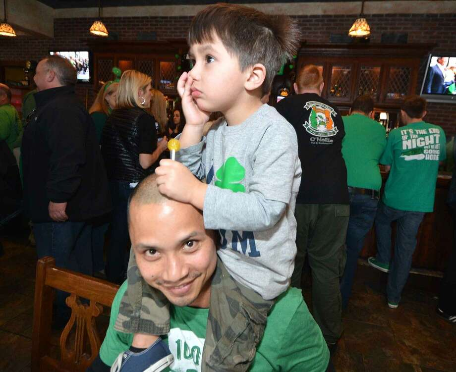 Hour Photo/Alex von Kleydorff Michael Nguyen Jr. sits on the shoulders of dad Michael Sr. as the family has lunch at O'Neill's Pub and Restaurant on St. Patricks Day