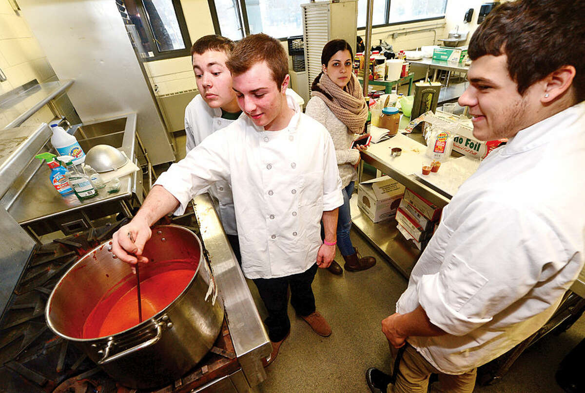 """Hour photo / Erik Trautmann Norwalk High School students Scott Castorina, Zach Grimm and Cody Mastropietro cook for the grand opening and ribbon cutting ceremony of the new Culinary Arts Café. The café will be a """"learning center"""" providing real world experiences and hands on activities for the students of Norwalk High."""