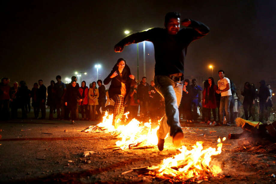 "In this picture taken on Tuesday, March 18, 2014, Iranians jump over bonfires during a celebration, known as ""Chaharshanbe Souri,"" or Wednesday Feast, marking the eve of the last Wednesday of the solar Persian year, in Pardisan park, Tehran, Iran. The festival has been frowned upon by hard-liners since the 1979 Islamic revolution because they consider it a symbol of Zoroastrianism, one of Iran's ancient religions of Iranians. They say it goes against Islamic traditions. (AP Photo/Ebrahim Noroozi)"