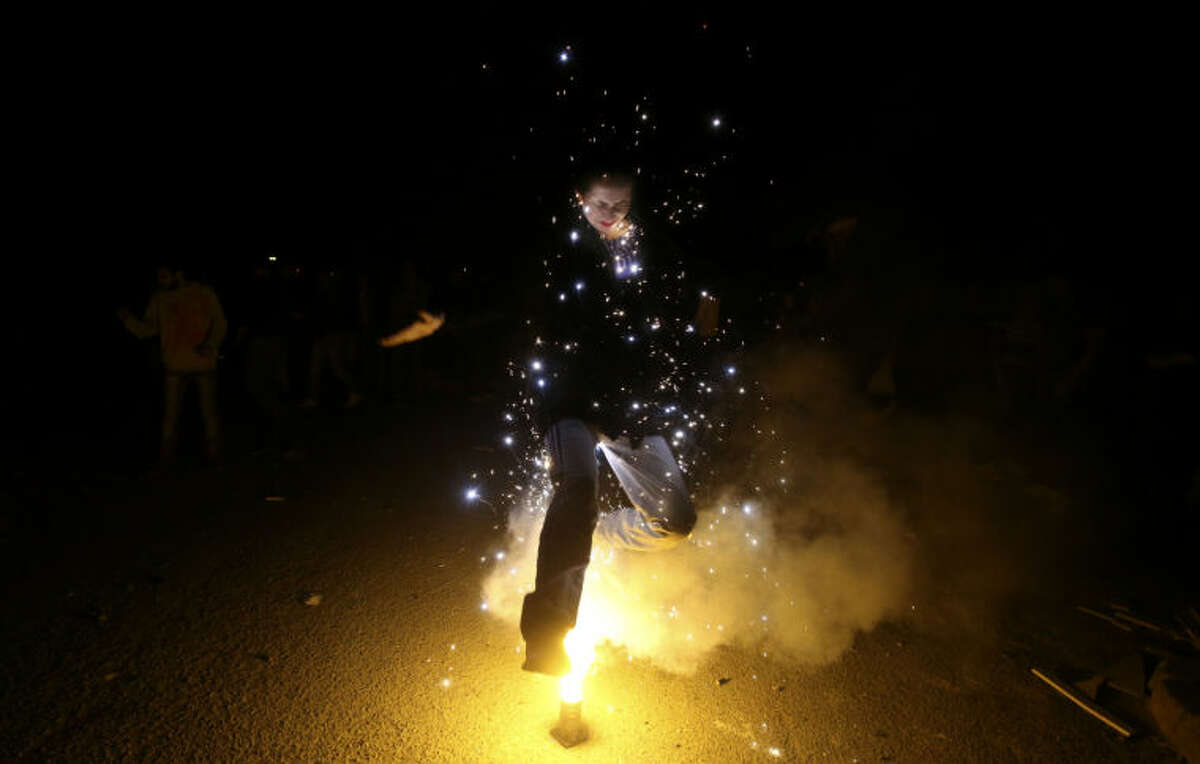 """In this picture taken on Tuesday, March 18, 2014, an Iranian woman jumps over a lit firework during a celebration, known as """"Chaharshanbe Souri,"""" or Wednesday Feast, marking the eve of the last Wednesday of the solar Persian year, in Pardisan park, Tehran, Iran. The festival has been frowned upon by hard-liners since the 1979 Islamic revolution because they consider it a symbol of Zoroastrianism, one of Iran's ancient religions of Iranians. They say it goes against Islamic traditions. (AP Photo/Vahid Salemi)"""