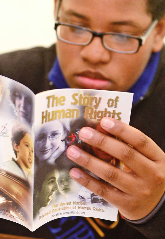 Hour photo / Erik Trautmann 7th grader Clive Bey reads about human rights during the Reerend Al Dancy's Pen or Pencil program at West Rocks Middle School that helps mentor 7th grade boys with discipline problems.