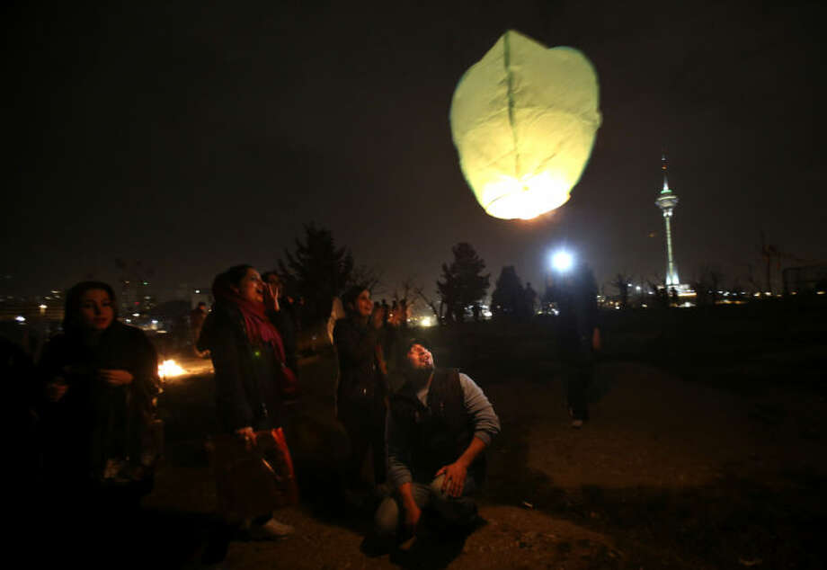 "In this picture taken on Tuesday, March 18, 2014, Iranians release a lit lantern during a celebration, known as ""Chaharshanbe Souri,"" or Wednesday Feast, marking the eve of the last Wednesday of the solar Persian year, in Pardisan park, Tehran, Iran. March 21, the first day of spring, marks Nowruz, the beginning of the year 1393 on the Persian calendar. (AP Photo/Vahid Salemi)"