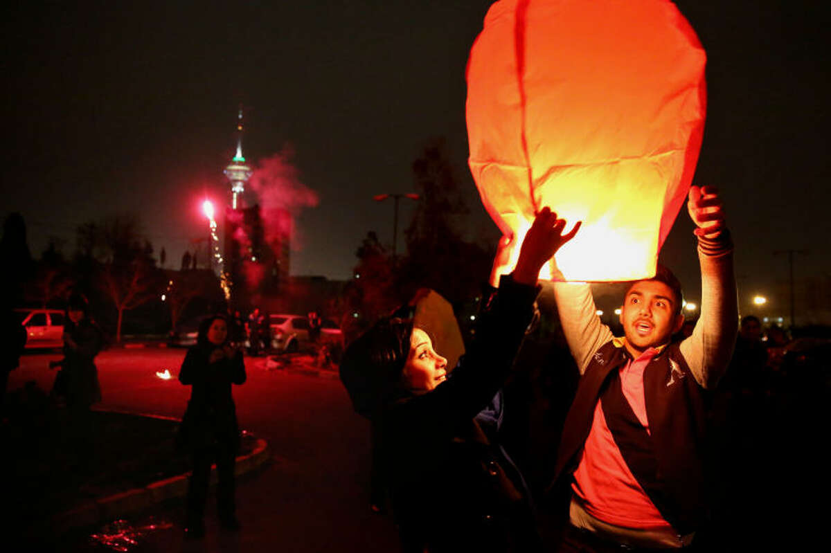 """In this picture taken on Tuesday, March 18, 2014, Iranian release a lit lantern during a celebration, known as """"Chaharshanbe Souri,"""" or Wednesday Feast, marking the eve of the last Wednesday of the solar Persian year, in Pardisan park, Tehran, Iran. March 21, the first day of spring, marks Nowruz, the beginning of the year 1393 on the Persian calendar. (AP Photo/Ebrahim Noroozi)"""