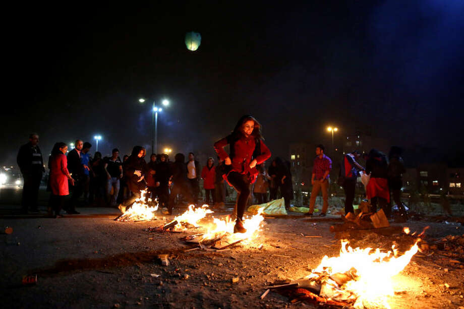"In this picture taken on Tuesday, March 18, 2014, an Iranian woman jumps over bonfires during a celebration, known as ""Chaharshanbe Souri,"" or Wednesday Feast, marking the eve of the last Wednesday of the solar Persian year, in Pardisan park, Tehran, Iran. The festival has been frowned upon by hard-liners since the 1979 Islamic revolution because they consider it a symbol of Zoroastrianism, one of Iran's ancient religions of Iranians. They say it goes against Islamic traditions. (AP Photo/Ebrahim Noroozi)"