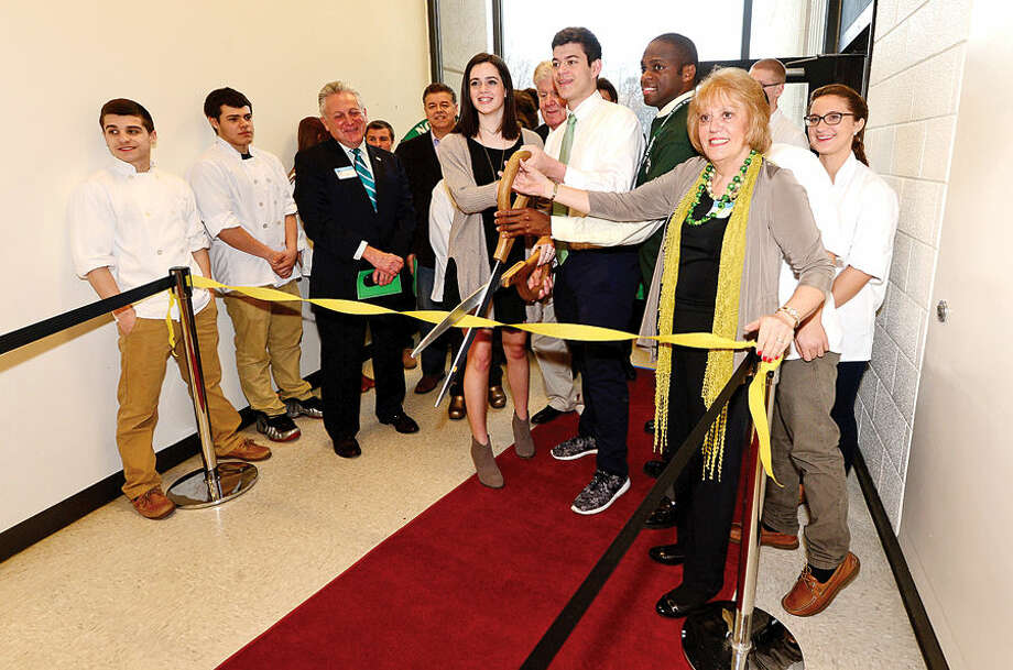 "Hour photo / Erik Trautmann Norwalk High School Housemaster Carol Marinaccio, Principal Reginald Roberts and seniors Anthony Granchelli and Claire Rudden cut the ribbon cutting for the grand opening of the new Culinary Arts Café. The café will be a ""learning center"" providing real world experiences and hands on activities for the students of Norwalk High."