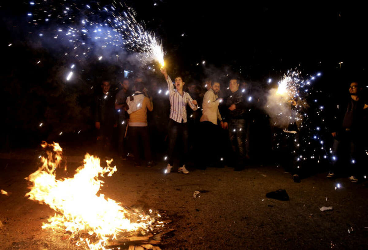"""In this picture taken on Tuesday, March 18, 2014, Iranians light fireworks during a celebration, known as """"Chaharshanbe Souri,"""" or Wednesday Feast, marking the eve of the last Wednesday of the solar Persian year, in Pardisan park, Tehran, Iran. The festival has been frowned upon by hard-liners since the 1979 Islamic revolution because they consider it a symbol of Zoroastrianism, one of Iran's ancient religions of Iranians. They say it goes against Islamic traditions. (AP Photo/Vahid Salemi)"""