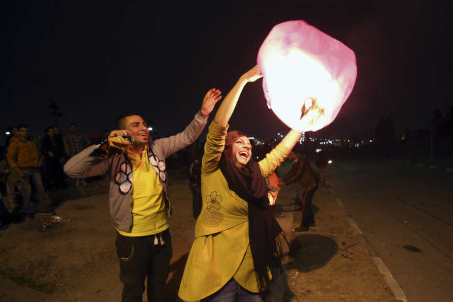 Two Iranians fly a wishing lantern in the Pardisan Park in Tehran, Iran, Tuesday, March 18, 2014, during Chaharshanbe Souri, or Wednesday Feast, an ancient Festival of Fire, on the eve of the last Wednesday of the year, when Iranians jump over burning bonfires and throw firecrackers celebrating arrival of the spring which coincides with their new year, or Nowruz, which begins on March 21. (AP Photo/Vahid Salemi)