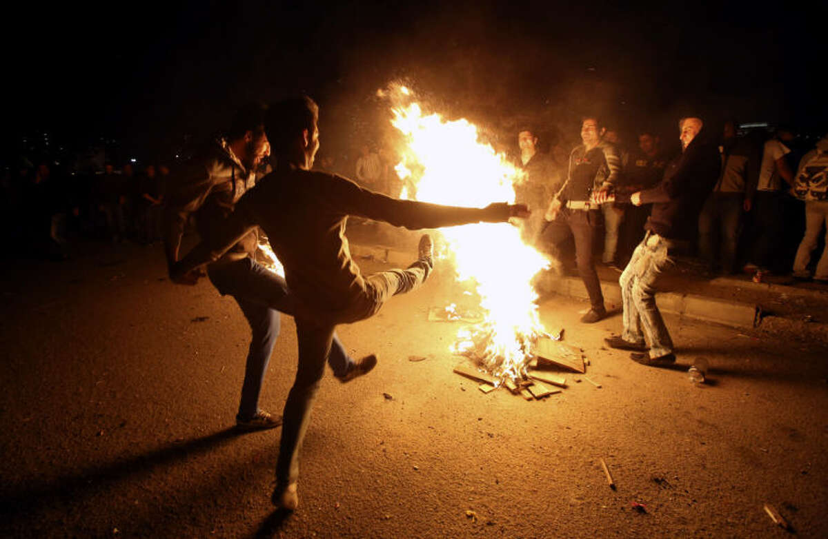 """In this picture taken on Tuesday, March 18, 2014, Iranians dance around a bonfire during a celebration, known as """"Chaharshanbe Souri,"""" or Wednesday Feast, marking the eve of the last Wednesday of the solar Persian year, in Pardisan park, Tehran, Iran. The festival has been frowned upon by hard-liners since the 1979 Islamic revolution because they consider it a symbol of Zoroastrianism, one of Iran's ancient religions of Iranians. They say it goes against Islamic traditions. (AP Photo/Vahid Salemi)"""
