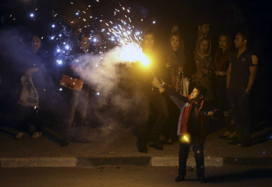 An Iranian boy holds a firework in the Pardisan Park in Tehran, Iran, Tuesday, March 18, 2014, during Chaharshanbe Souri, or Wednesday Feast, an ancient Festival of Fire, on the eve of the last Wednesday of the year, when Iranians jump over burning bonfires and throw firecrackers celebrating arrival of the spring which coincides with their new year, or Nowruz, which begins on March 21. (AP Photo/Vahid Salemi)